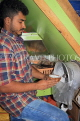 BAHRAIN, Manama, Central Market area, Asian small shops, man scraping coconut, BHR1324JPL