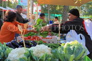 BAHRAIN, Noor El Ain, Garden Bazaar, Farmers Market, shopper at vegetable stall, BHR1783JPL