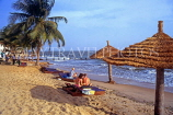 GAMBIA, Banjul, beach with coconut trees, sunbathers and thatched sunshades, GAM901JPL