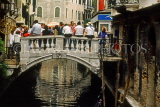 Italy, VENICE, small bridge over canal, and people seated on it, ITL1902JPL