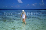 MALDIVE ISLANDS, Coral reef, exposed coral at low tide and tourist paddling, MAL684JPL