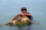 MEXICO, Yucatan, COZUMEL, man with turtle at sea, MEX526JPL