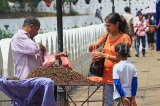 SRI LANKA, Kandy, Kandy lakeside, fruitseller, people buying Velvet Tamarind (Gal Siyambala), SLK3954JPL