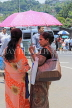 SRI LANKA, Kandy, town centre, two women chatting under umbrella, SLK4039JPL