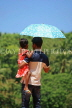 SRI LANKA, Kandy area, father and daughter, with umbrella under mid day sun, SLK2496JPL