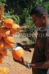 SRI LANKA, Kandy area, roadside stall selling King Coconut (Thambili), vendor cutting fruit, SLK2551JPL
