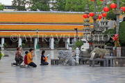 THAILAND, Bangkok, WAT SUTHAT, courtyard statues, and worshippers, THA3216JPL